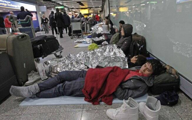 Passageiros descansam deitados no chão do Terminal 3 do Aeroporto de Heathrow, em Londres