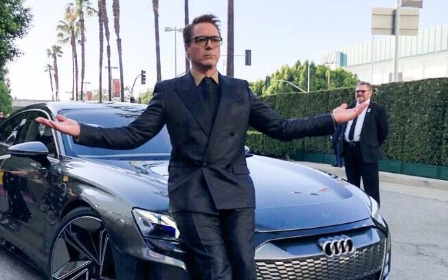 robert downey jr posa ao lado de carro