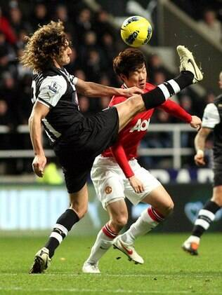 O meia Park, do Manchester United, disputa bola com o zagueiro Coloccini, dos New Castle